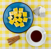 Yellow Turkish delight in plate, cup of tea and cinnamon. Yellow Turkish delight in blue plate, cup of tea and cinnamon sticks on tablecloth, top view Stock Images