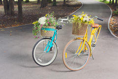 Yellow and turqoise city woman bicycles with flowers in park Stock Photo