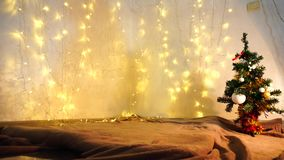 Yellow twinkling  garlands and Christmas tree. Cord with garlanded winking LED lights hung on white wall. Decorated evergreen  with toys in corner. Concept of stock video