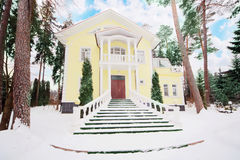 Yellow two-storey cottage with columns in woods Royalty Free Stock Photo