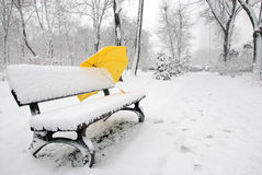 Yellow umbrella. Lying on a bench after snowing Stock Photo