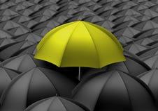 Yellow umbrella above black umbrellas Stock Photos