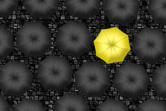 Yellow umbrella. Bright yellow umbrella among set of black umbre Stock Image