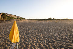 Yellow umbrella closed on sandy beach at sunset Royalty Free Stock Photography
