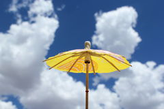Yellow Umbrella. Yellow cocktail umbrella on a cloudy day royalty free stock image