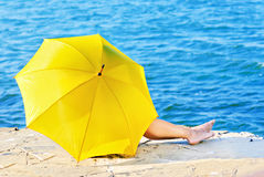 Yellow umbrella is covering a girl by the sea Stock Photography