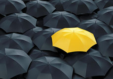 Yellow umbrella among dark ones Royalty Free Stock Images