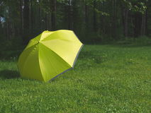 He yellow umbrella. A yellow umbrella in a grass lawn with dark forrest in the background Stock Photography