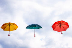 Yellow Umbrella, Green Umbrella  and Red Umbrella floating in the Air Stock Image
