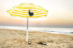 Yellow umbrella lonely on the beach at sunset in Puglia Royalty Free Stock Images