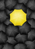 Yellow umbrella standing out from the rest Stock Image