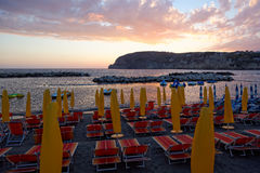Yellow umbrellas and chaise longue on empty sandy beach at sunset, Ischia, Italy Stock Photo