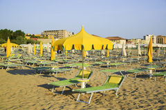 Yellow umbrellas and chaise lounges on the beach of Rimini in Italy. The destination in the Adriatic coast of Emilia-Romagna stock images