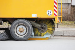Yellow urban sweeper cleans road from dirt with a round brush in the spring. Stock Photo
