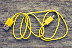 Yellow USB cable on wooden table Royalty Free Stock Images