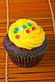 Yellow vanilla cupcake with confetti stars Stock Image