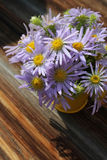 Yellow vase with bouquet of meadow purple daisies on wooden back Royalty Free Stock Images