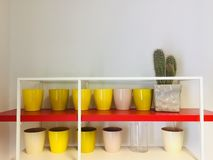 Yellow vases on a red shelf royalty free stock images