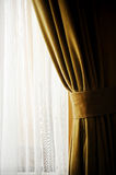 Yellow velvet window curtain. Detail with a yellow velvet window curtain shot against outdoor light Royalty Free Stock Photo