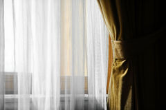 Yellow velvet window curtain. Detail with a yellow velvet curtain shot against outdoor light Stock Image