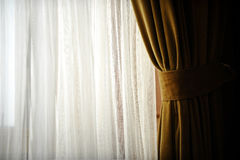 Yellow velvet window curtain. Detail with a yellow velvet window curtain shot against outdoor light Stock Photos