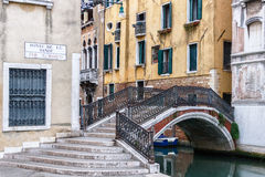 Yellow Venetian street corner with an arch railed bridge. VENICE, ITALY - MARCH 31, 2016: A yellow Venetian street corner with an arch railed bridge over a Stock Photo