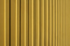 Yellow vertical wood siding. Macro of yellow vertical wood siding in full sunlight royalty free stock image