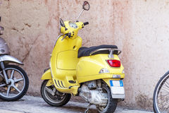 Yellow Vespa  scooter on the street in Italy Royalty Free Stock Photos