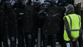 Yellow vests - Gilets jaunes protests - Protester standing alone in front of riot police stock image