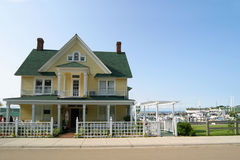 Yellow Victorian home. Yellow Victorian-style house with green roof. Blue sky and marina with sailboats in background Stock Images