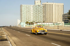 Yellow vintage american car in front of two Hotels Stock Image