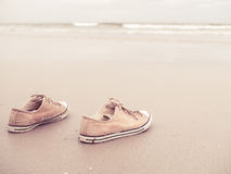 Yellow vintage canvas shoes on the sand beach Stock Image