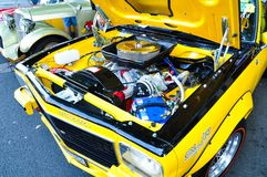 Yellow Vintage car opens the hood showing its engine at Classic motor show on Australia day. stock image
