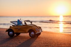 Yellow vintage car with two surfboards. On the beach at sunset Stock Images