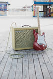 Yellow vintage guitar aplifier with cable and red electric guitar Royalty Free Stock Photography