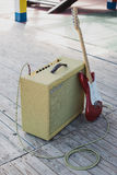 Yellow vintage guitar aplifier with cable and red electric guitar Stock Photos