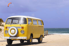 Yellow Van - Vintage, Sand Beach, Water, Holidays. Yellow van and a orange inflatable kite for kiteboarding, Peniche beach, Portugal Royalty Free Stock Photos