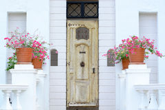 Yellow vintage wooden door on white wall. Background Royalty Free Stock Photography