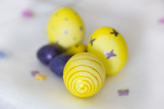 Yellow and violet Easter eggs with had drawings of butterflies,. Polka dots and spiral Royalty Free Stock Image