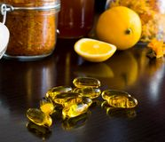 Yellow vitamin capsules, on background lemon. Cold prevention. Golden capsules on foreground and lemon, honey and spices on background Stock Photo