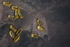 Yellow vitamin capsules on a dark background, soft gelatin capsu Stock Image