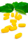 Yellow vitamin pills over green leaves Royalty Free Stock Images