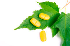 Yellow vitamin pills over green leaves Royalty Free Stock Photo