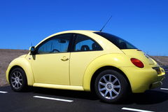 Yellow Volkswagen Beetle - side back view. Almere Poort, Flevoland, The Netherlands - June 6, 2015: Yellow Volkswagen Beetle parked in a public parking lot in Stock Photos