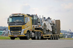 Yellow Volvo FH Hauls Heavy Machinery. FORSSA, FINLAND - SEPTEMBER 20, 2014: Yellow Volvo FH 500 hauls heavy NCC machinery. NCC produces various services that Stock Images