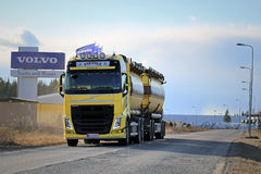 Yellow Volvo FH Tank Truck on the Road with Volvo Trucks Sign Stock Photo