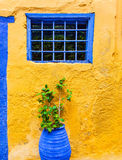 Yellow wall with blue window and pot plant  in the old street on Greece. Greek style Stock Images