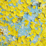 Yellow wall covered with scraps of paint Stock Photos
