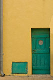 Yellow wall and the green door Stock Photography
