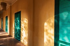 Yellow wall and green doors with sun light rays. Shot in Thang Long Citadel in the imperial city, Hanoi, Vietnam. Yellow wall and green doors perspective with royalty free stock image